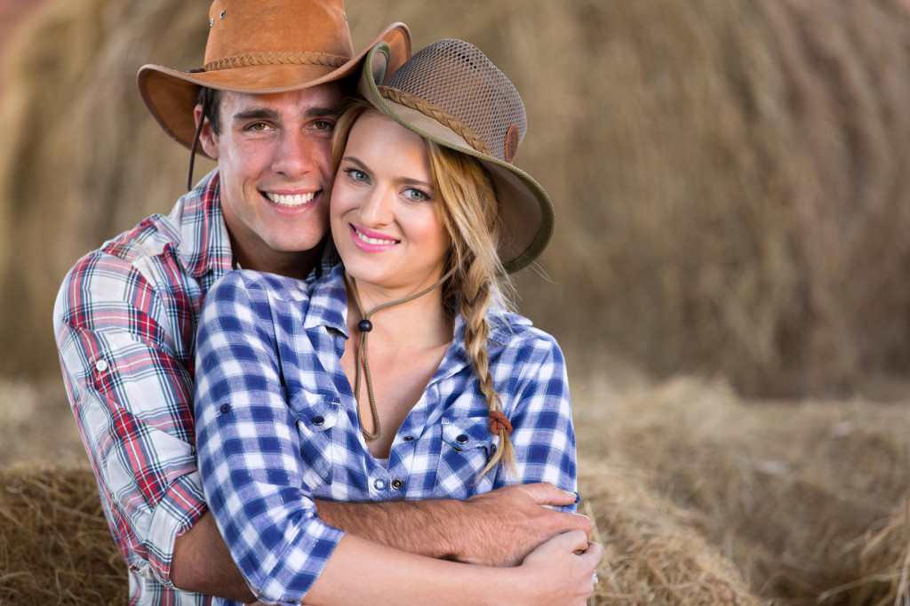 portrait of young cute farming couple hugging in barn